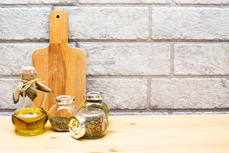 水罐橄榄油、切板和香料在瓶子 免版税图库摄影