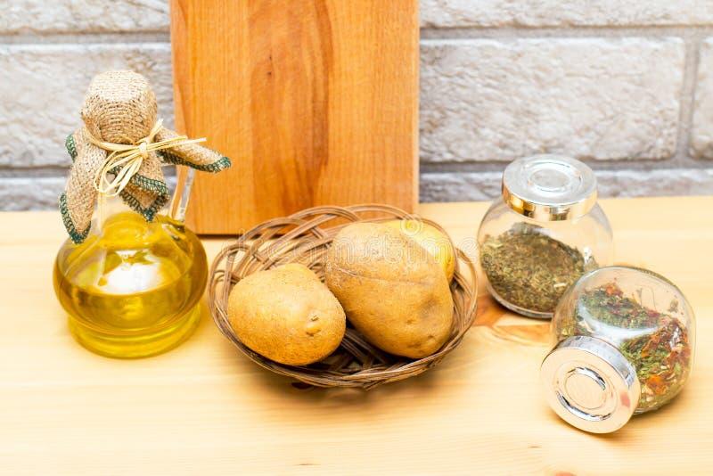 水罐橄榄油、土豆、切板和香料在瓶子 免版税库存照片