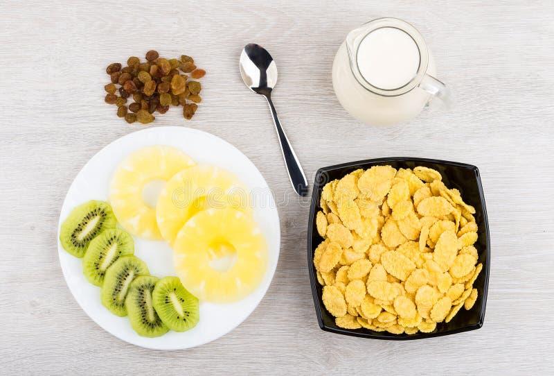 水罐牛奶、碗有玉米片的,菠萝和猕猴桃 免版税图库摄影