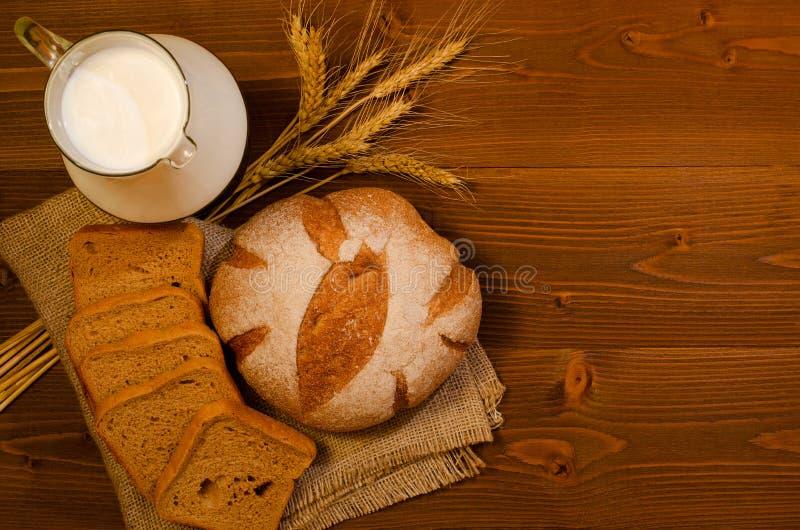 水罐用牛奶,在周围和方形的黑麦面包和耳朵在木桌,顶视图上 库存照片