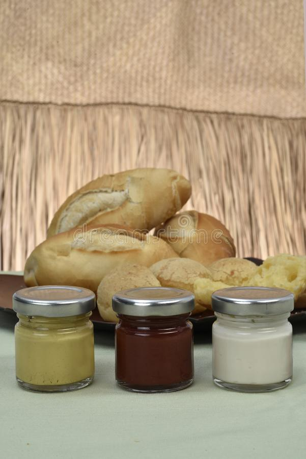 罐用蛋黄酱和番茄酱与paes在背景中 免版税库存照片
