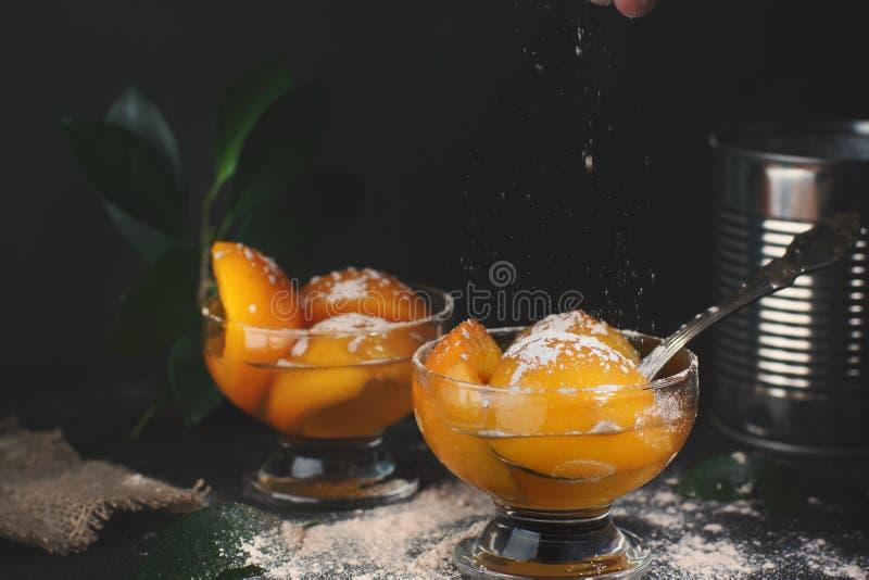 罐装桃子用在一个碗的糖浆在黑暗的背景,在与匙子的锡罐附近,洒在上面,行动的糖粉  库存照片