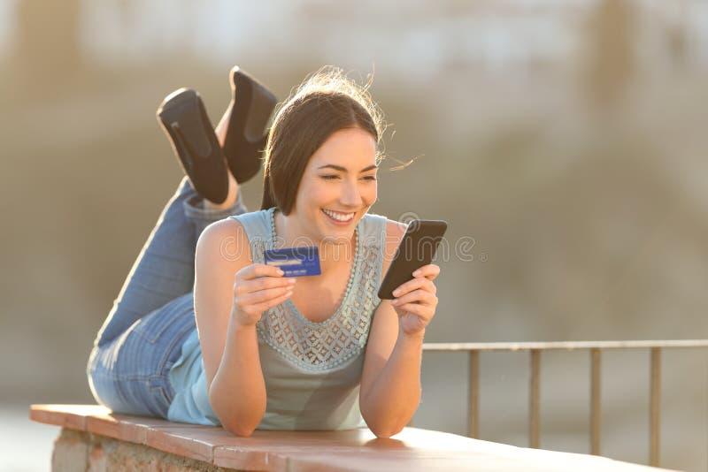 网上买家支付与信用卡和电话 免版税图库摄影