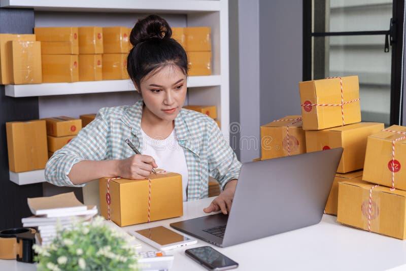 网上企业主,妇女与手提电脑一起使用小包箱子为做准备交付到顾客 免版税图库摄影