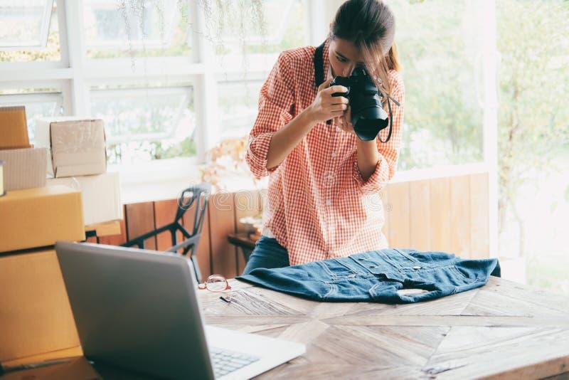 网上卖主所有者拍产品照片加载的到网站网上商店 网上卖,网络购物和电子商务 库存图片