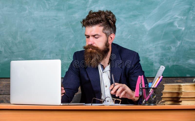 网上学校和教育 遥远的教育的概念 老师有胡子的成熟人在网上教使用膝上型计算机和 免版税库存照片