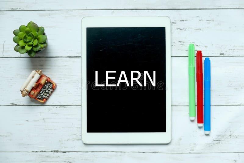 网上数字学会技术教育概念 植物顶视图,五颜六色的笔和片剂写与在白色木学会 库存照片