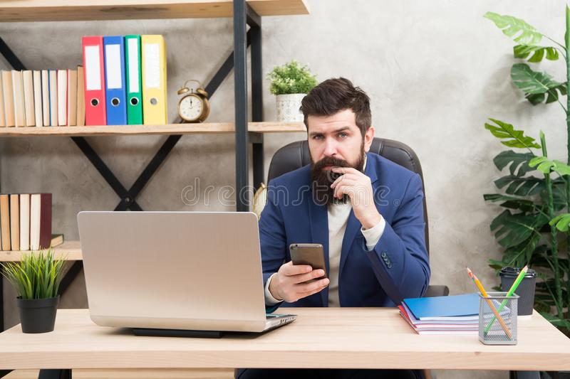 网上查寻 人有胡子的上司经理坐有膝上型计算机的办公室 解决业务问题的经理 负责的商人 免版税库存照片