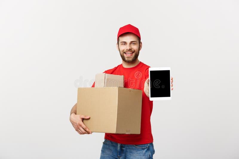网上购物、交付、技术和生活方式概念-当前片剂和拿着箱子的微笑的送货人 库存图片