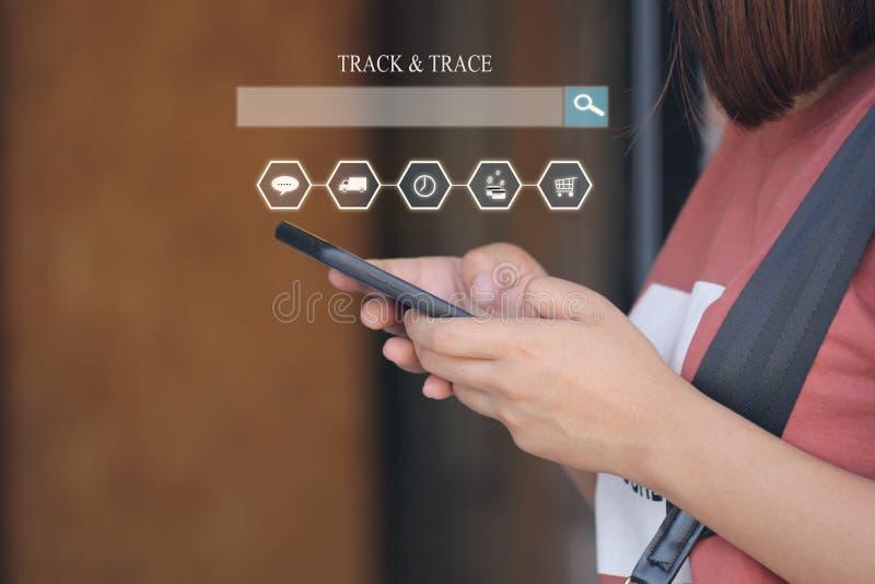 网上购物,拿着巧妙的电话和跟踪同水准的妇女手 免版税库存照片