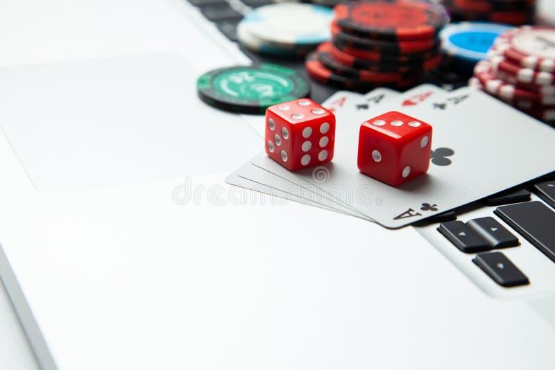 网上赌博娱乐场膝上型计算机 膝上型计算机键盘和芯片与模子和纸牌在一张绿色赌桌上 赌博比赛的瘾 免版税库存照片