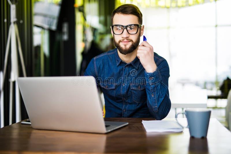 网上付款 供以人员拿着信用卡和使用在木书桌上的膝上型计算机网上购物的 看照相机 免版税库存照片