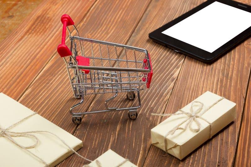 网上购物概念-空的购物车、膝上型计算机和片剂个人计算机,在土气木背景的礼物盒 库存图片