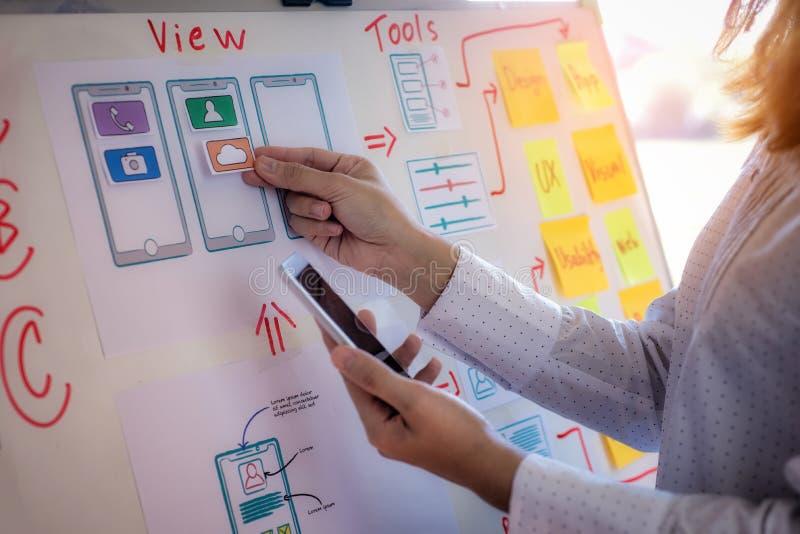网做测试对手机的设计师妇女略图申请在办公室 用户经验设计观念 库存照片