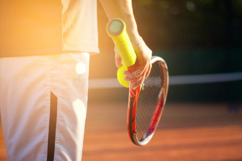网球员准备服务网球在与阳光的一次比赛期间在背景中 库存图片