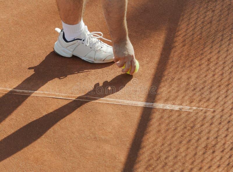 网球员法庭上得到球 免版税库存图片