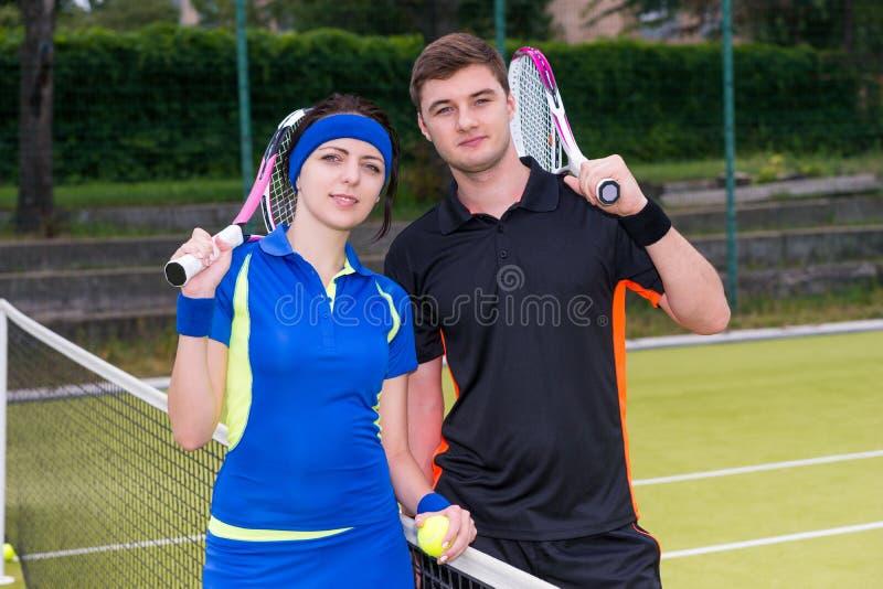 网球员年轻夫妇拿着一副球拍和一个球在t的 免版税库存照片