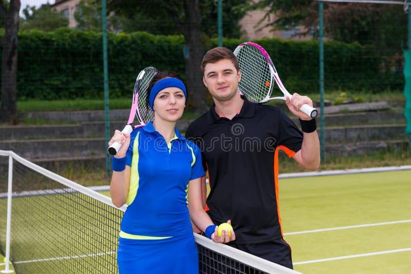 网球员年轻有吸引力的夫妇拿着球拍的和 免版税库存照片