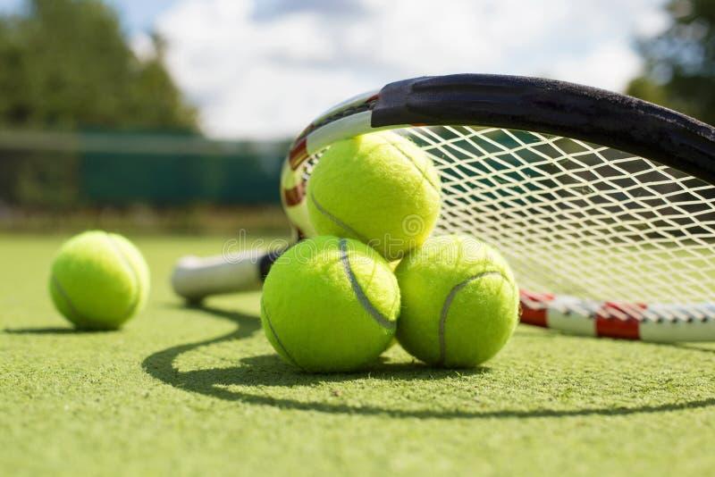 网球和球拍在草地网球场 免版税库存照片