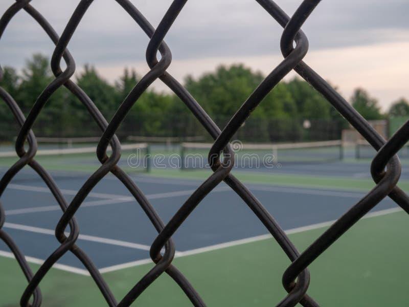 网球场在与构筑在前景的黑篱芭的背景中 免版税库存图片