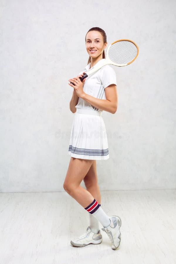 网球服的美丽的女孩,站立与网球拍 免版税库存照片
