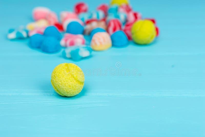 以网球的形式鲜美糖果在木桌上 图库摄影