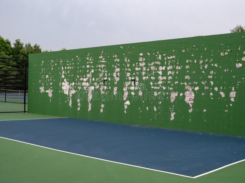 网球,曲棍网兜球,球炫耀实践墙壁在与绿色油漆削皮的一个地方法院 库存照片