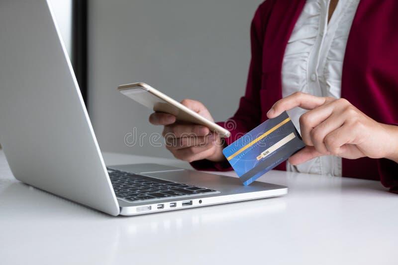 网络购物和付款的消费者拿着信用卡的女商人和智能手机在互联网做购买 免版税库存图片