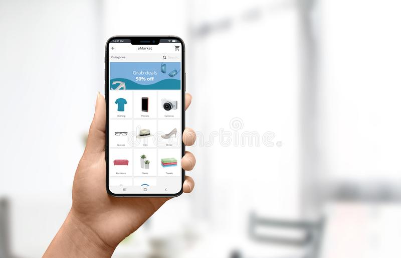 网络购物在家概念 妇女藏品电话和为飞翅产品使用现代网络商店网站 免版税库存照片
