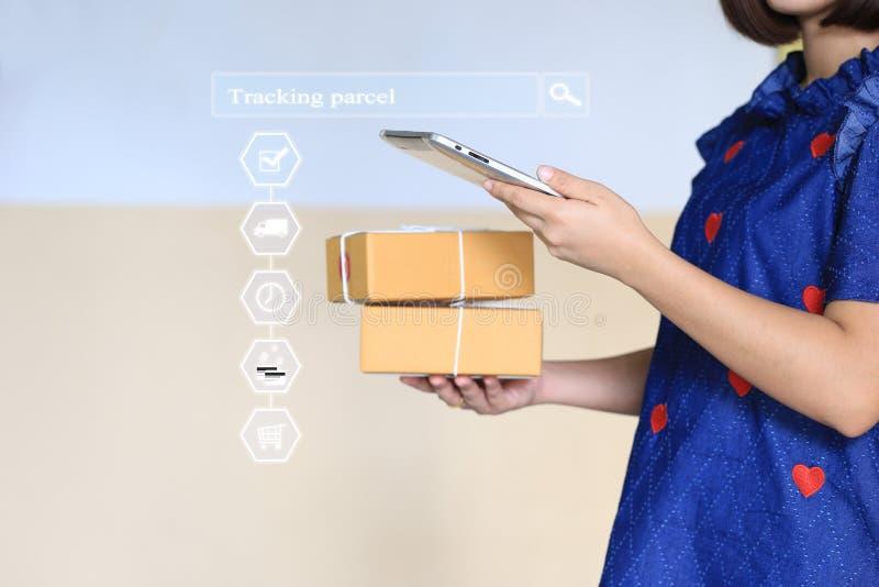 网络购物,妇女手藏品智能手机和在网上跟踪小包更新与全息图、电子商务和交付的状态 免版税库存照片