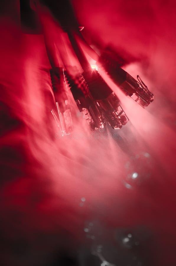 网络转接和以太网电缆,全球性通信的标志 色的网络在与光和smo的黑暗的背景缚住 库存照片