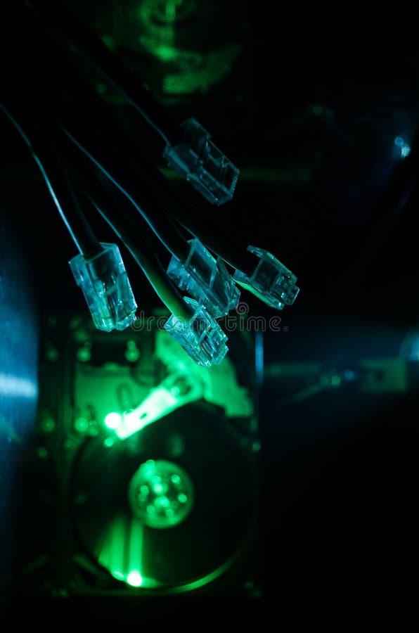 网络转接和以太网电缆,全球性通信的标志 色的网络在与光和smo的黑暗的背景缚住 图库摄影