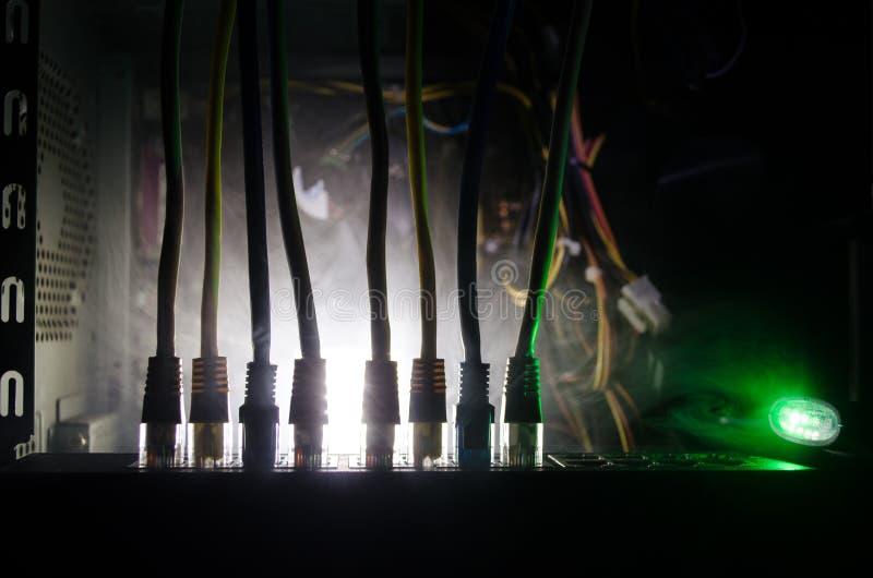 网络转接和以太网电缆,全球性通信的标志 色的网络在与光和smo的黑暗的背景缚住 库存图片