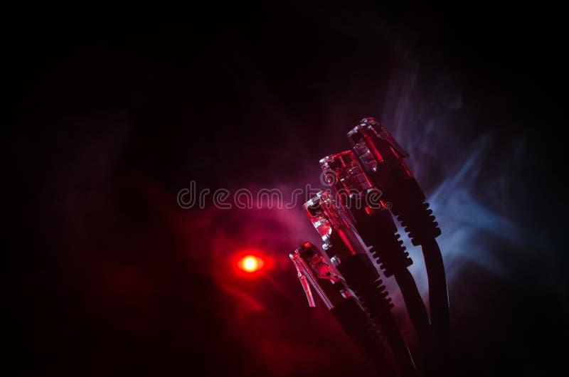 网络转接和以太网电缆,全球性通信的标志 色的网络在与光和smo的黑暗的背景缚住 免版税库存照片