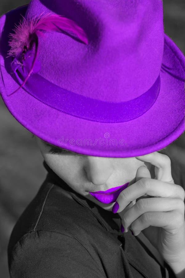 紫罗兰色帽子的妇女。紫罗兰色嘴唇和修指甲。 免版税图库摄影
