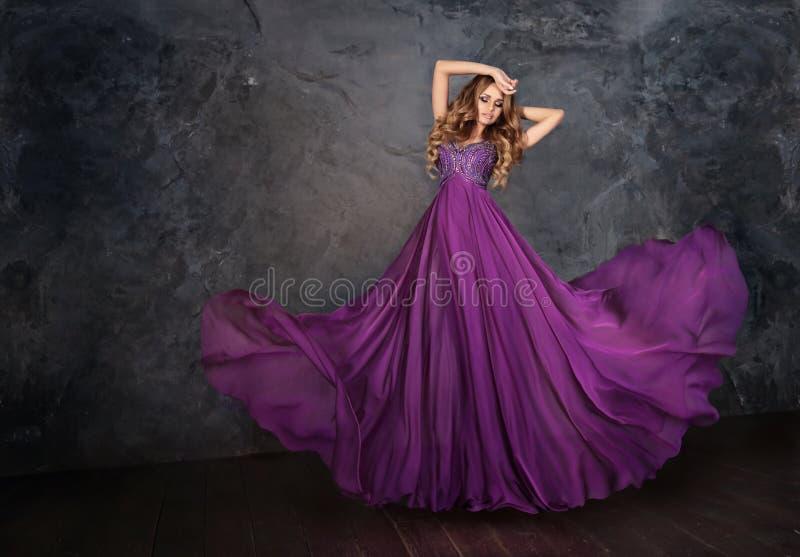 紫罗兰色礼服的一名妇女 库存图片
