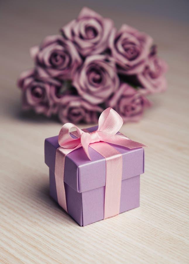 紫罗兰色花和礼物盒有桃红色丝带的 库存照片