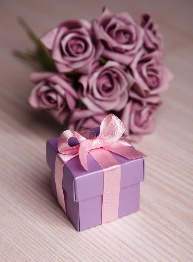 紫罗兰色花和礼物盒有桃红色丝带的 库存图片