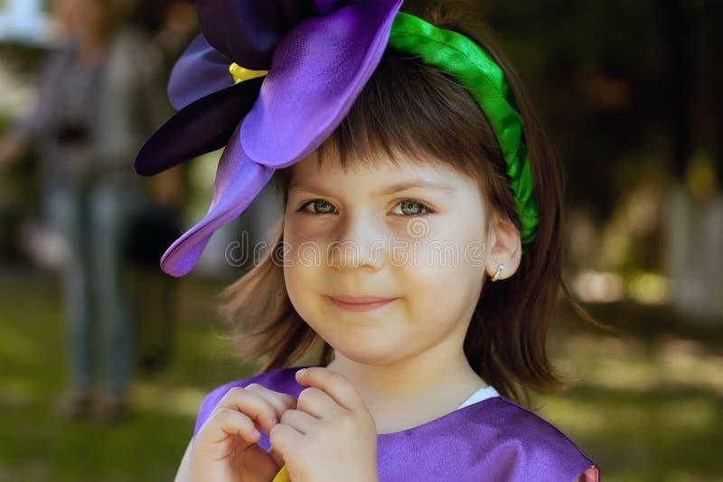 紫罗兰色花衣服的小女孩微笑着 免版税库存图片