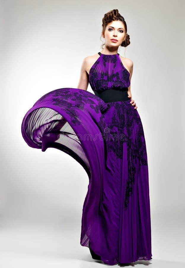 紫罗兰色长的礼服的美丽的时尚妇女 免版税库存图片
