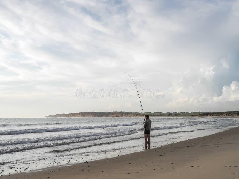罗安达,安哥拉- 2014年4月26日:站立在渔的罗安达,安哥拉,非洲北部的海滩的消遣年轻渔夫 免版税库存图片