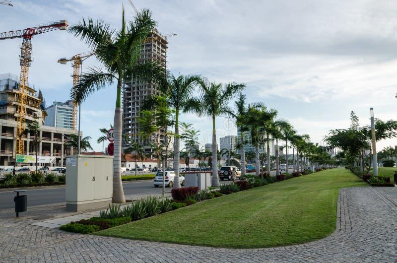 罗安达,安哥拉- 2014年4月28日:罗安达有现代高层建筑物的棕榈和建筑的` s散步在海边 库存图片