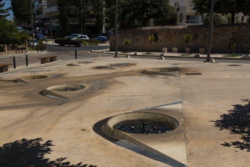 罗希姆诺,希腊- 2016年7月29日:在帆柱附近寺庙的喷泉  库存照片