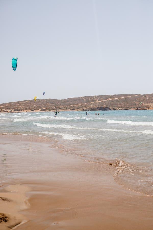 罗得岛海岛,PRASSONISI海滩,2018年7月23日,希腊 实践Kitesurfing的未认出的kitesurfers在的爱琴海海滩 图库摄影