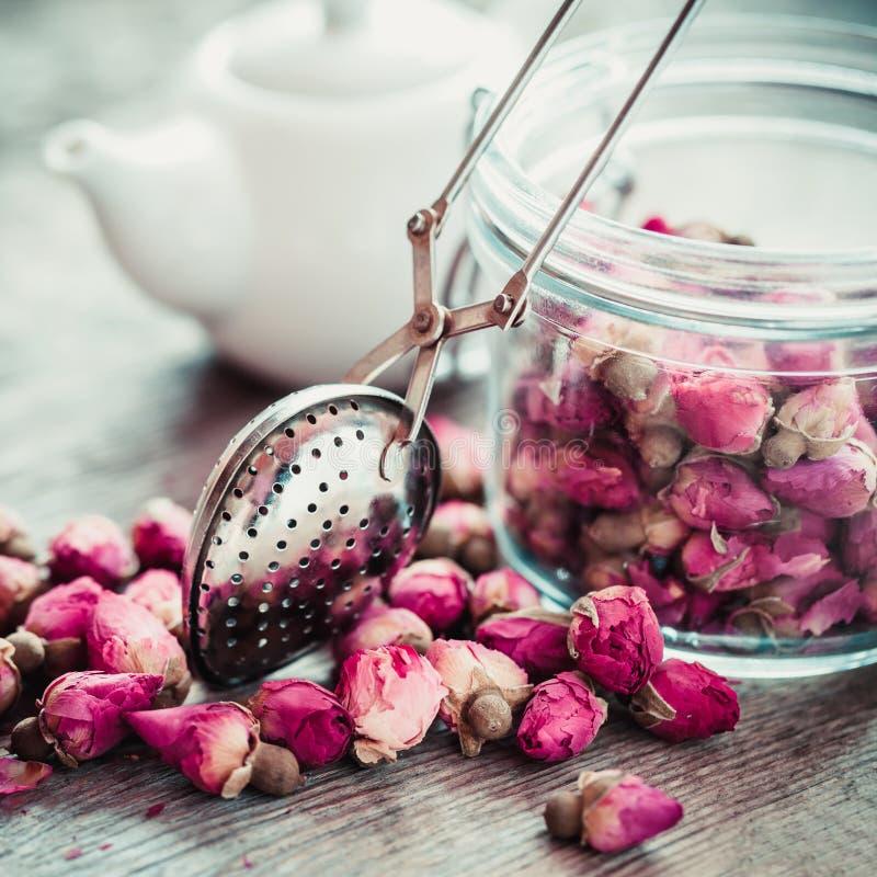罗斯发芽茶、茶infuser、玻璃瓶子和茶壶在背景 免版税图库摄影