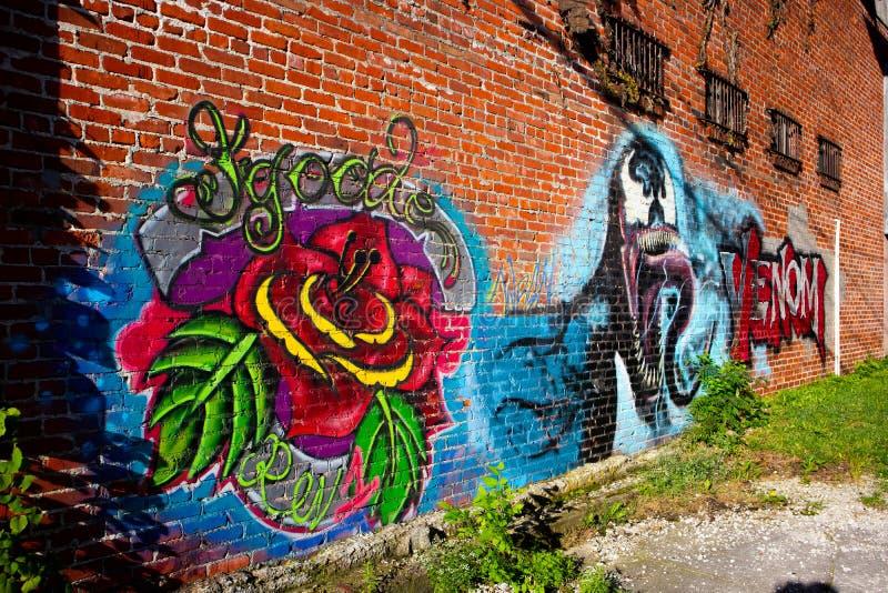 罗斯和毒液在砖墙上的街道画艺术 免版税库存图片