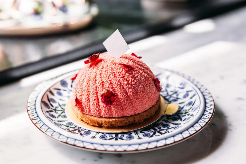罗斯和Lychee奶油甜点结块用玫瑰花瓣和白色巧克力板材装饰在蓝色和白色瓷板材 库存照片