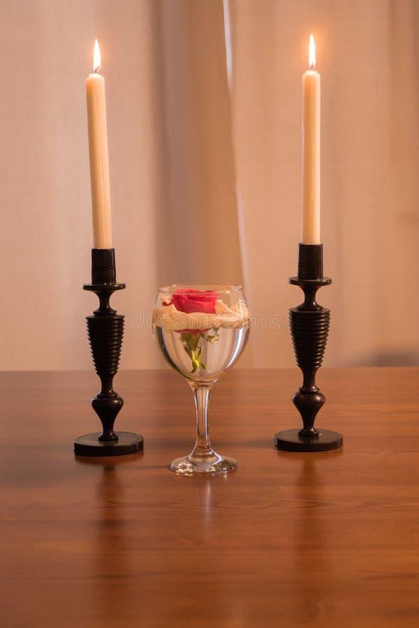 罗斯在玻璃和蜡烛 库存照片