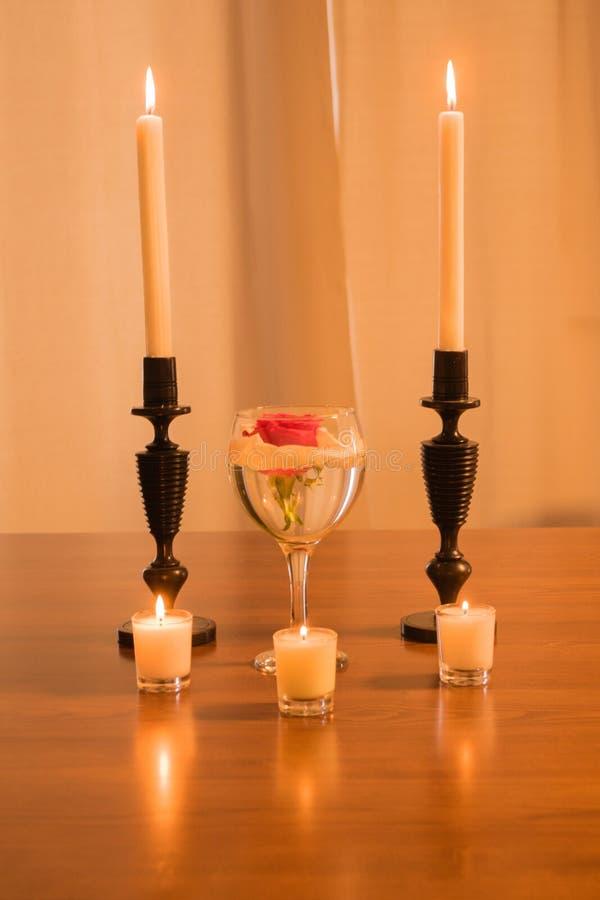 罗斯在玻璃和蜡烛 免版税库存照片