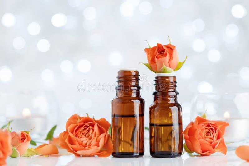 罗斯在白色桌上的精油瓶与bokeh作用 温泉,芳香疗法,健康,秀丽背景 免版税库存照片